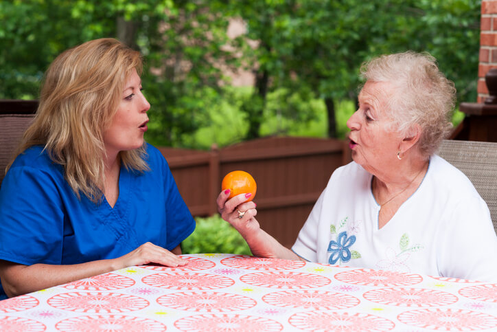 SLP working with senior patient to say orange